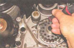 Отверткой выводим конец пружины из-за прилива корпуса масляного насоса