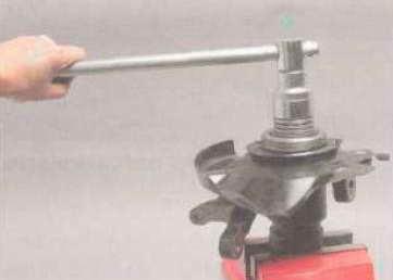 Чашечным съемником выпрессовываем из поворотного кулака подшипник.