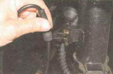 Вынимаем из прорези кронштейна амортизаторной стойки резиновый держатель проводов датчика.