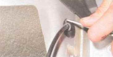 Отверткой проталкиваем в сторону арки колеса резиновый чехол провода.